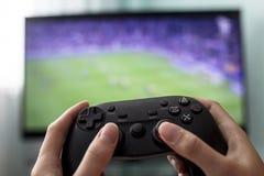 De vrouwelijke handen houden de bedieningshendel op de achtergrond van TV, een spel van voetbal, close-up, een meisje een gamer royalty-vrije stock foto's