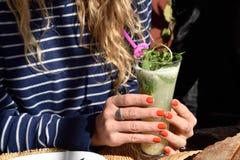 de vrouwelijke handen houden een glas van cocktail Stock Afbeeldingen