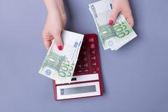 De vrouwelijke handen houden EURO rekeningen en een calculator op een blauwe achtergrond - het concept boekhouding Stock Afbeelding