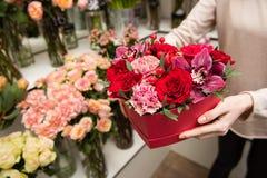De vrouwelijke handen houden rode doos met bloemen stock foto's