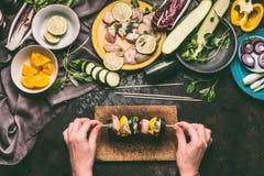 De vrouwelijke handen Kippenvlees houden en de groenten die doorsteken op scherpe raad op de donkere achtergrond van de keukenlij Royalty-vrije Stock Foto's