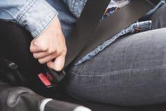 De vrouwelijke handen maken de veiligheidsgordel in de auto vast royalty-vrije stock foto