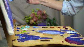 De vrouwelijke handen mengen kleuren op het palet en de verf op het canvas zijaanzicht, een beetje langzame motie stock footage
