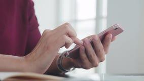 De vrouwelijke handen met een horloge en een keurige manicure houden smartphone stock videobeelden