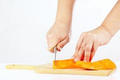 De vrouwelijke handen met een mes hakt wortel op een scherpe raad stock afbeelding