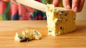De vrouwelijke handen met een mes verwijderen kaas met schimmel op een houten raad 4K Langzame Motie stock video