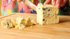 De vrouwelijke handen met een mes verwijderen kaas met schimmel op een houten raad 4K Langzame Motie stock videobeelden