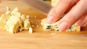 De vrouwelijke handen met een mes verwijderen kaas met schimmel op een houten raad 4K Langzame Motie stock footage