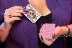 De vrouwelijke handen met een purpere manicure houden een dek van spelkaarten royalty-vrije stock foto