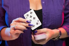 De vrouwelijke handen met een purpere manicure houden een dek van spelkaarten royalty-vrije stock afbeelding