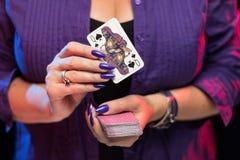 De vrouwelijke handen met een purpere manicure houden een dek van spelkaarten royalty-vrije stock afbeeldingen