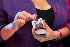 De vrouwelijke handen met een purpere manicure houden een dek van spelkaarten stock foto