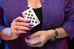 De vrouwelijke handen met een purpere manicure houden een dek van spelkaarten stock afbeelding