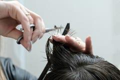 De vrouwelijke handen met schaar snijden de einden van het haar op het kerel` s hoofd af Close-up van kapsels in een kapper royalty-vrije stock foto's