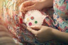 De vrouwelijke handen naaien wit katoenen hart met knopen verschillende kleuren Met de hand gemaakt het concept liefde Valentine& Royalty-vrije Stock Foto