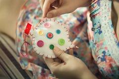 De vrouwelijke handen naaien wit katoenen hart met knopen verschillende kleuren Met de hand gemaakt het concept liefde Valentine& Royalty-vrije Stock Afbeelding