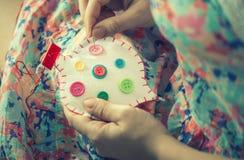 De vrouwelijke handen naaien wit katoenen hart met knopen verschillende kleuren Met de hand gemaakt het concept liefde Valentine& Royalty-vrije Stock Foto's