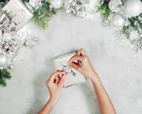 De vrouwelijke handen openen of verpakkende huidige doos Giften, sparrentak en snuisterijenornamenten op grijze steenlijst Feeste stock afbeelding