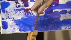 De vrouwelijke handen schilderen met borstel het canvas met blauwe olieverf stock footage