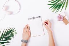 De vrouwelijke handen schrijven in een notitieboekje bij het bureau Stock Afbeeldingen