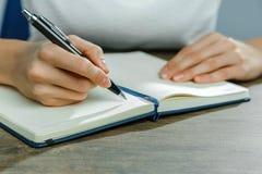 De vrouwelijke handen schrijven in een notitieboekje stock foto's