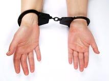 De vrouwelijke handen shackled in handboeien Stock Foto's