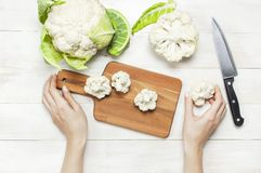 De vrouwelijke handen snijden bloemkool met mes op scherpe raad, legt de keukenhanddoek op rustieke witte houten achtergrond hoog stock afbeelding