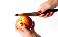 De vrouwelijke handen snijden een appel met een mes op een witte achtergrond Stock Afbeeldingen