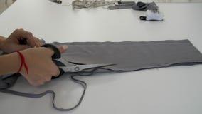 De vrouwelijke handen snijden een stuk van grijze doek door een schede af stock video