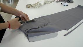 De vrouwelijke handen snijden een stuk van grijze doek door een schede af stock videobeelden