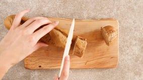 De vrouwelijke handen snijden verse roggebaguette op de houten scherpe raad stock videobeelden