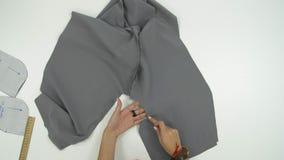 De vrouwelijke handen tonen iets op grijze doek stock video