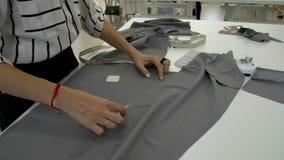 De vrouwelijke handen tonen iets op grijze doek stock footage