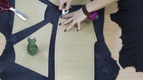 De vrouwelijke handen trekt overzicht rond het document patroon van kleren over de stof door het krijt stock video