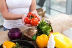 De vrouwelijke handen van een Kaukasische kok die rode tomaat houden bundelen over keuken worktop met vers kruidenierswinkel en r Stock Afbeeldingen