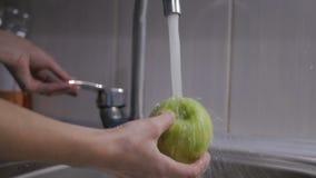 De vrouwelijke handen wassen de groene appel onder de kraan Vrouwen jonge huisvrouw die verse groene appel in keuken wassen onder stock video