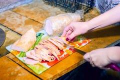 De vrouwelijke handenchef-koks snijden vlees met een mes in de keuken in een restaurant stock afbeelding