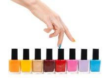 De vrouwelijke handvingers zijn het gekleurde vervenpoetsmiddel stock foto's