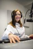 De vrouwelijke Hoofdtelefoons van Jockeysmiling while wearing in Radiostudio stock fotografie