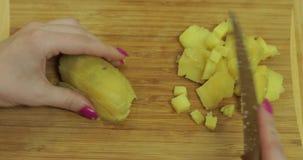 De vrouwelijke huisvrouw overhandigt snijdende aardappels in stukken in de keuken stock videobeelden