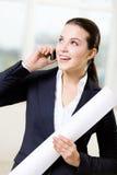 De vrouwelijke ingenieur met blauwdruk spreekt op telefoon Royalty-vrije Stock Foto