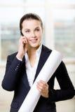 De vrouwelijke ingenieur met lay-out spreekt op telefoon Royalty-vrije Stock Afbeelding