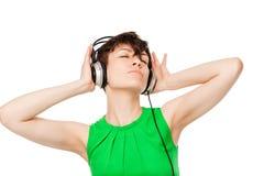 De vrouwelijke 25 jaar, houdt van aan muziek met hoofdtelefoons te luisteren Royalty-vrije Stock Fotografie