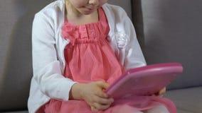 De vrouwelijke jong geitje het spelen stuk speelgoed bank van de tabletzitting, kinderjarenvrije tijd, onderwijsstuk speelgoed stock videobeelden