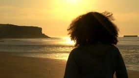 De vrouwelijke jonge vrouw van de meisjestiener met krullend haar die zich op een strand bevinden die zonsondergang of zonsopgang stock videobeelden