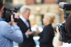De Vrouwelijke Journalist Interviewing B van fotograaftaking pictures of royalty-vrije stock foto's