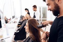 De vrouwelijke kapper maakt bruin haar aan mooie vrouw recht gebruikend haarijzer in schoonheidssalon stock afbeelding