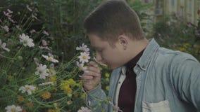De vrouwelijke kerel snuift bloemen stock footage