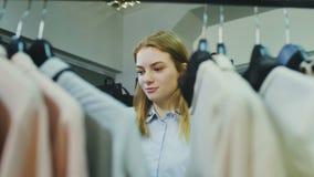 De vrouwelijke klant bekijkt goederen op rek in kledingsopslag stock footage
