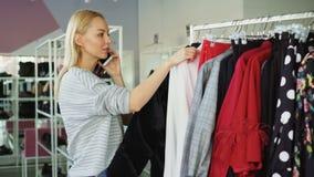 De vrouwelijke klant gaat langzaam door modieuze kleren op hanger in ruime winkel Andere klanten bewegen zich stock videobeelden